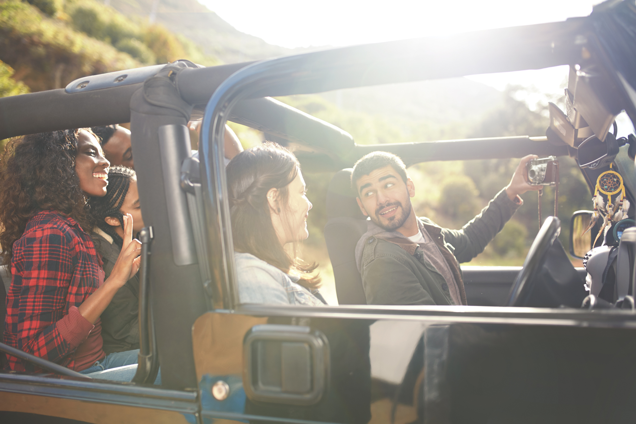 Man with digital camera taking selfie in jeep with friends